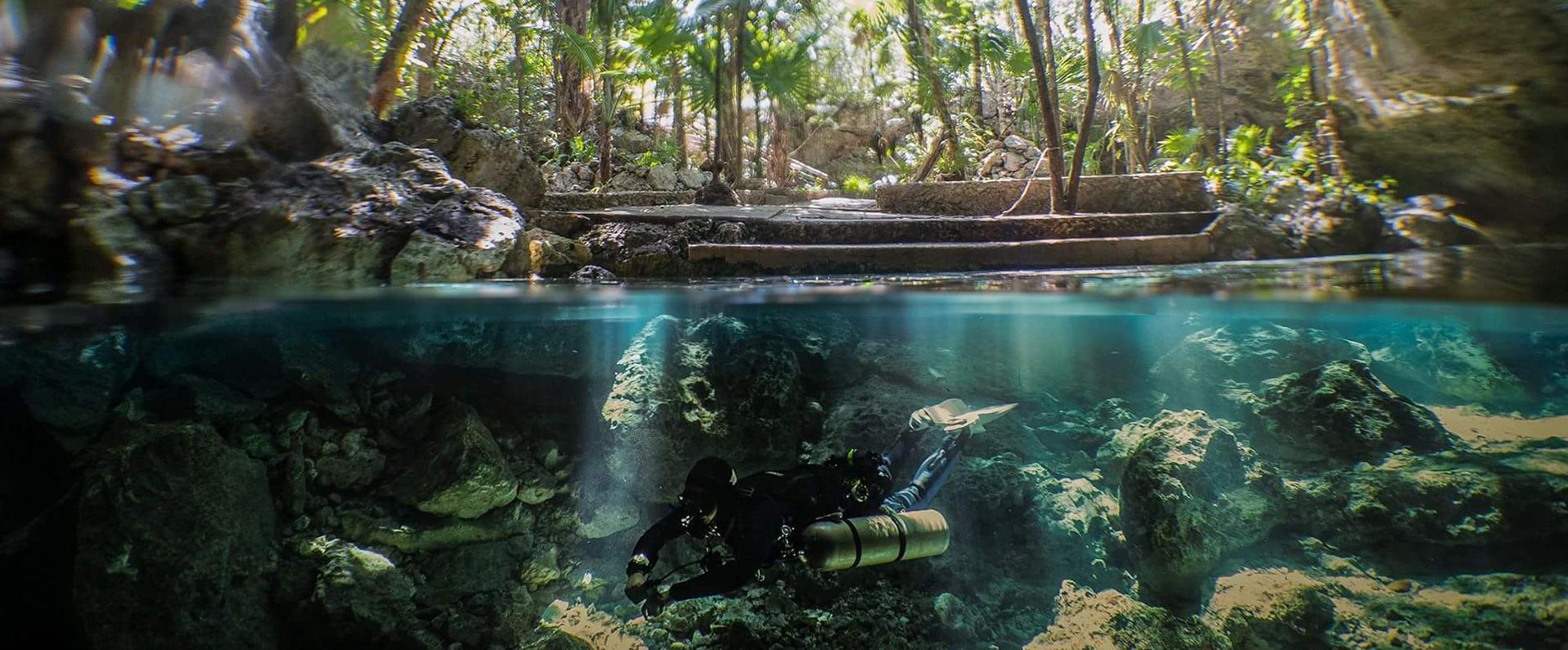 Half underwater photo of diver in cenote