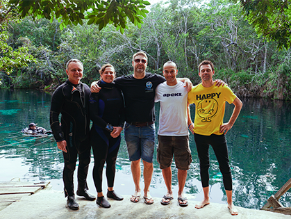 Photo of several people posing by a lake